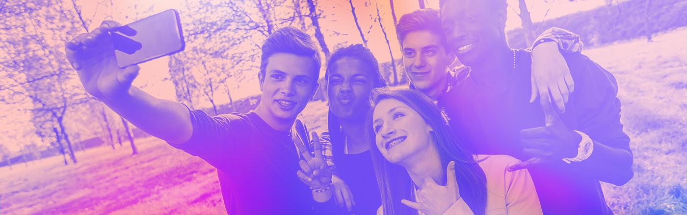 Group of five friends taking selfie outside