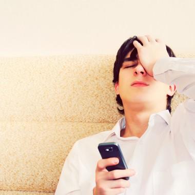 Boy looking regretful holding a phone