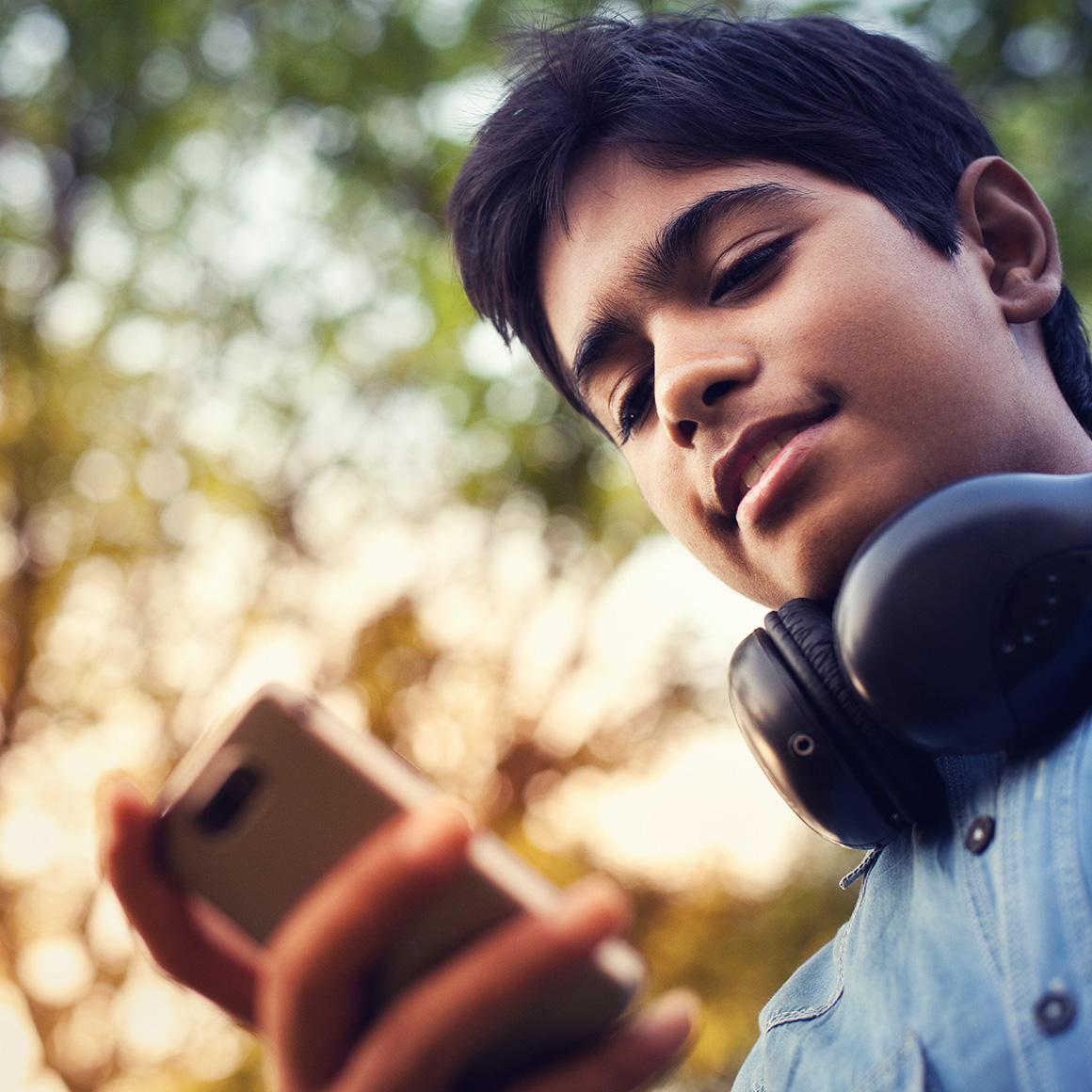 Boy wearing headphones looking at phone